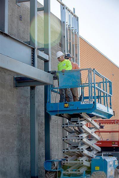 Staff Members On Site Using Scissor Lift